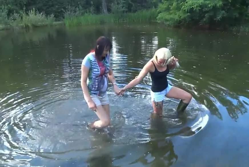 Bi-Freundinnen gehen Hand in Hand in Gummistiefeln durch den Schlamm